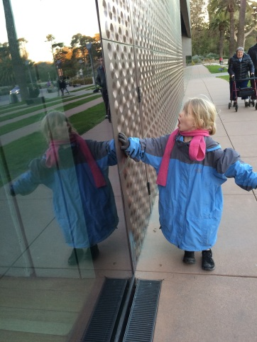 Boy in giant jacket looking at his reflection