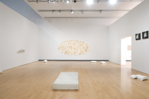 Installation view that focuses on what appears to be a cheap and well-worn mattress, but it is hand-carved from white marble